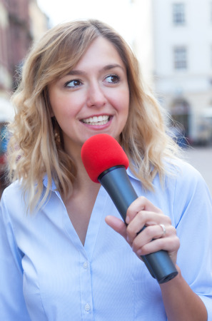 respondent: Young woman with blond hair and microphone Stock Photo