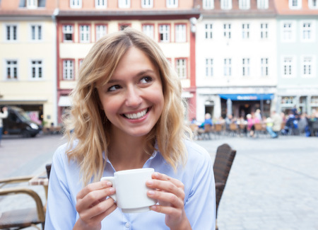 blond hair: Woman with blond hair drinking a coffee and looking around