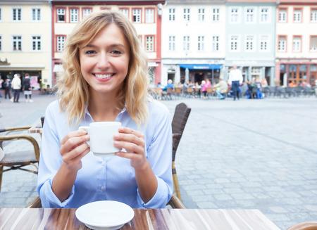 cabello rubio: Mujer con el pelo rubia disfrutando de un caf� caliente