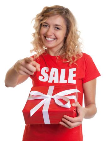 cabello rubio: Se�alando mujer con el pelo rubio y un regalo en una venta-shirt Foto de archivo