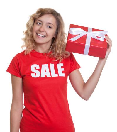 cabello rubio: Mujer con el pelo rubio y un regalo en las ventas-shirt