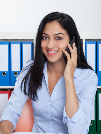 Laughing turkish businesswoman with phone at office photo