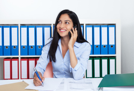 Aantrekkelijke Turkse onderneemster met telefoon op kantoor