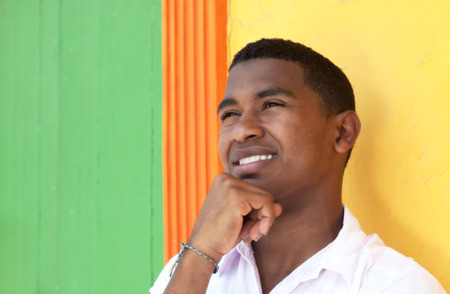 visions of america: Thinking caribbean guy in front of a colorful wall