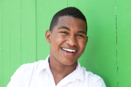Laughing caribbean guy in front of a green wall