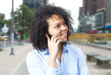 latina america: Attractive hispanic woman in the city at phone - Blick rechts