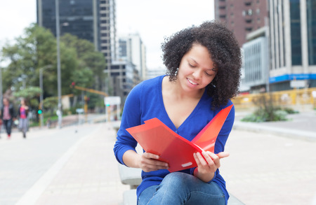 Latin student with curly hair reading document in the city photo