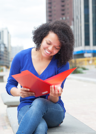 Laughing latin student with curly hair reading document in the city photo