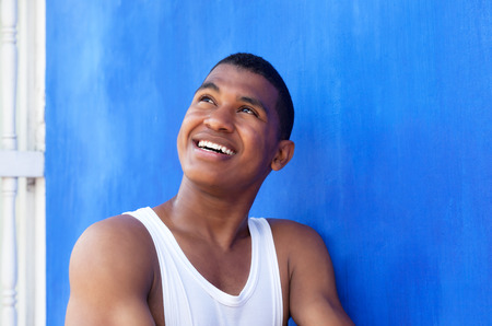 Thinking latin guy in front of a blue wall