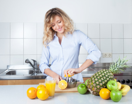 Woman with curly blond hair preparing orang juice in the kitchen photo