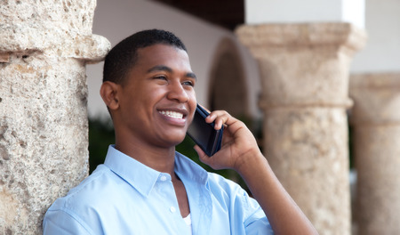 Lachen latin man met telefoon in een koloniale stad