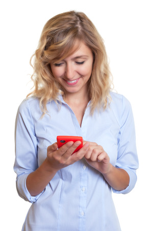 Woman with curly blond hair writing message with phone