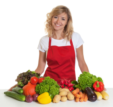 german food: Happy housewife with red apron and fresh vegetables Stock Photo