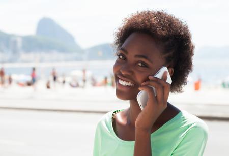 Laughing brazilian woman at Rio de Janeiro at phone