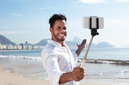 personas tomando agua: Hombre brasileño haciendo selfie con un palo en la playa de Copacabana