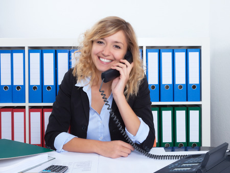 sales call: Blond businesswoman at office speaking with client at phone Stock Photo
