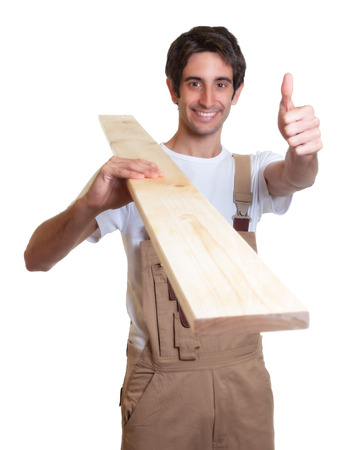 Laughing carpenter with wooden beam showing thumb photo