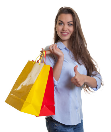 Attractive woman with long dark hair and shopping bags showing thumb photo