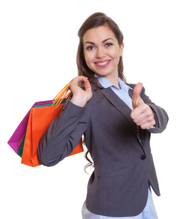 Fashionable woman with shopping bags showing thumb up photo