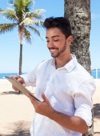 e book: Happy brazilian guy reading e book with tablet at beach