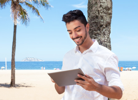e book: Laughing brazilian guy reading e book with tablet at beach