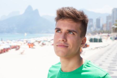 Dreaming sporty guy in a green shirt at beach