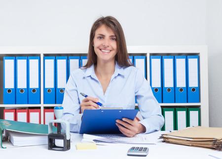 secretaria: Secretaria feliz con el pelo largo y castaño en el trabajo en la oficina