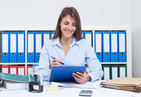 capelli castani: Segretario con lunghi capelli castani al lavoro in ufficio