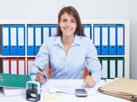 capelli castani: Ridere segretario con lunghi capelli castani in ufficio