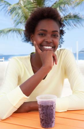 brazilian woman: Laughing brazilian woman at beach with soda Stock Photo