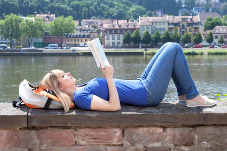 girl studying: Woman with blonde hair reading a book on a river