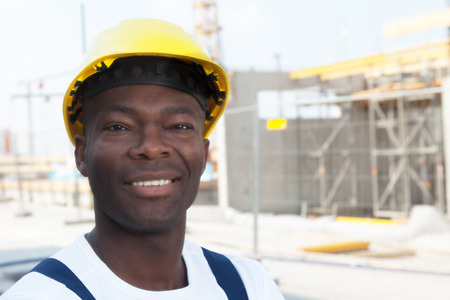 Happy african american construction worker at building site