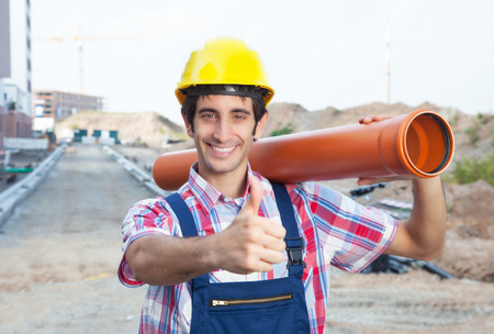 dug well: Hispanic construction worker with pipe at building site showing thumb Stock Photo