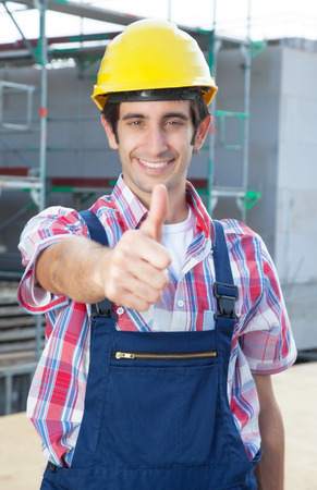 dug well: Hispanic construction worker at building site with showing thumb up