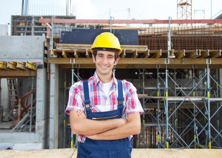 white collar worker: Happy hispanic construction worker at building site
