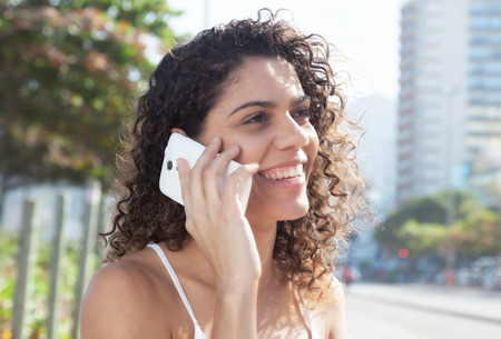 latina america: Latin woman in the city speaking at phone