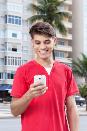 mobile sms: Hispanic guy in the city typing message at phone Stock Photo
