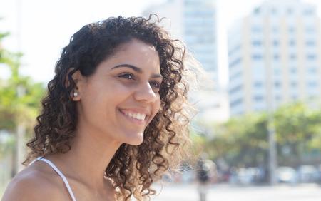 Lachende Latijnse vrouw buiten in een stad van Latijns-Amerika met moderne gebouwen en bomen op de achtergrond Stockfoto
