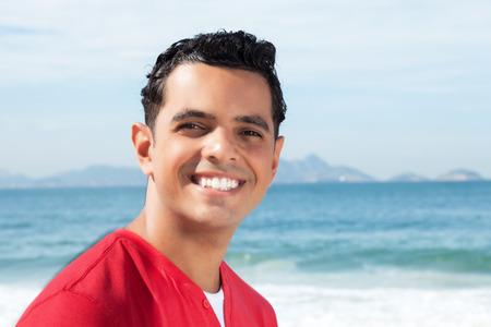 Laughing latin guy at beach looking at camera