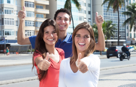 Three young people in the city showing thumb up