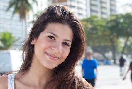 Mujer sonriente con el pelo oscuro en la ciudad