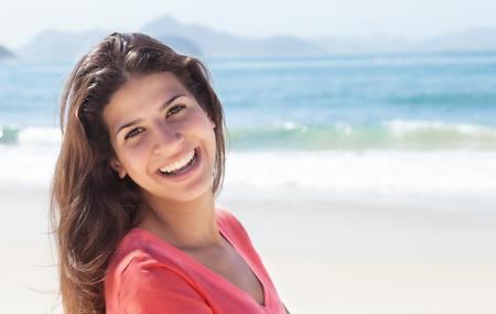 mujer sola: Mujer divertida con el pelo oscuro en la playa Foto de archivo