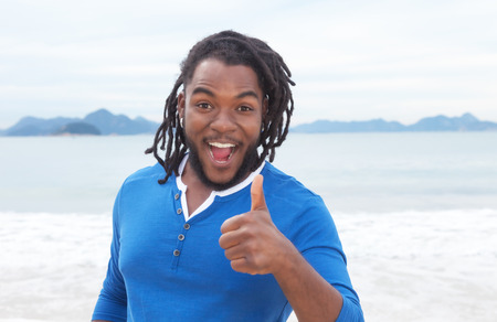 reggae: African american guy with dreadlocks at beach showing thumb up Stock Photo