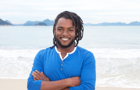 African american guy with dreadlocks and crossed arms at beach