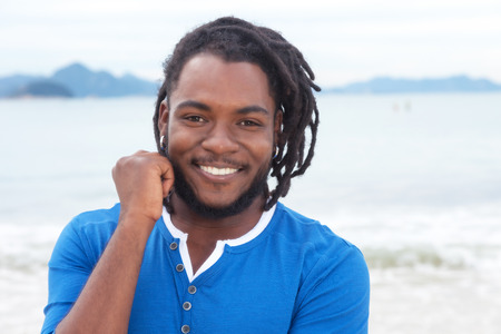 jamaican adult: Laughing african american guy with dreadlocks at beach Stock Photo
