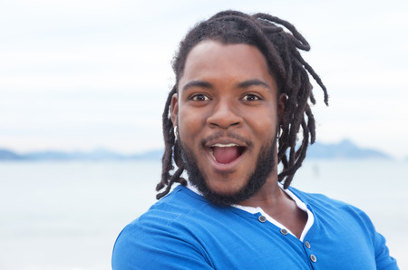 reggae: Happy african american guy with dreadlocks at beach