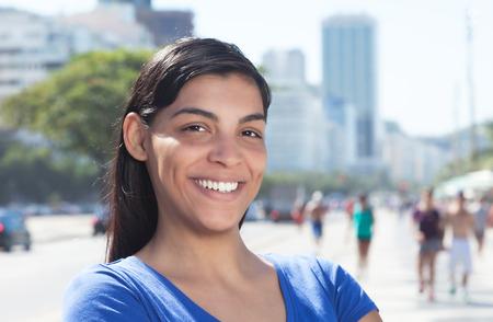 Lachen Latijnse vrouw met lang donker haar in de stad Stockfoto