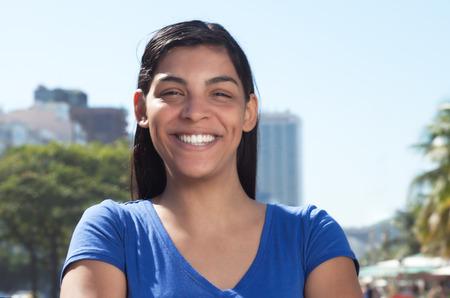 Latijnse vrouw met lang donker haar in de stad op zoek naar camera