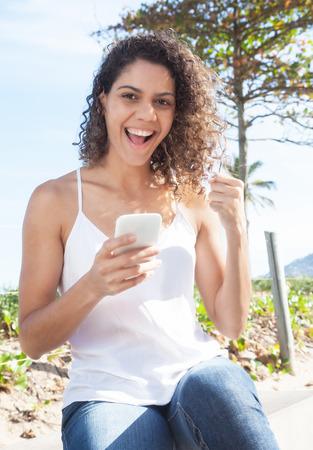 latina america: Latin woman receiving good news at phone