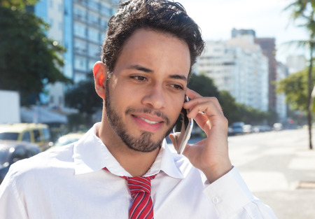american banker: Handsome latin businessman at phone in the city